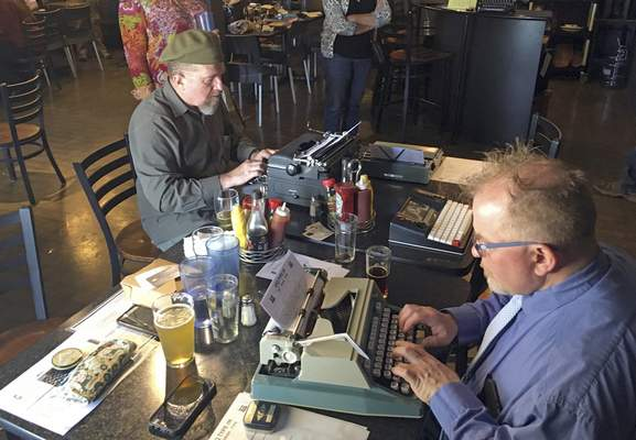 Associated Press photos Joe Van Cleave, left, and Rich Boucher try out vintage typewriters in April at a type-in, social gatherings in public places where typewriter fans test different vintage machines, in Albuquerque, N.M.