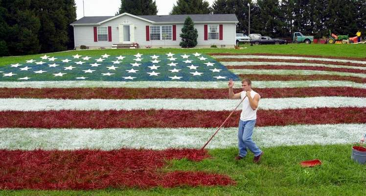 Samuel Hoffman | The Journal Gazette From Sept. 18, 2001: John Morris waves to a passer-by Monday as he helps paint a 60-by-100 foot flag on the lawn of South Milford neighbor Lori Davis. Davis' son, Chad, a Marine lance corporal, was arriving home Monday on leave. Others with loved ones in the military will be allowed to inscribe their names on the flag's stars.