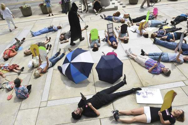 """Demonstrators stage a """"die-in"""" Tuesday outside the E. Ross Adair Federal Building and U.S. Courthouse in downtown Fort Wayne to protest proposals to repeal and replace the Affordable Care Act. The protest took place outside the building that houses the offices of Republican Sen. Todd Young."""