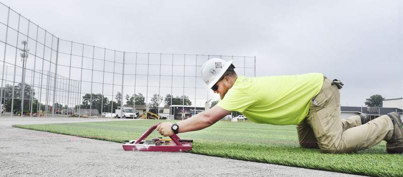 Cathie Rowand | The Journal Gazette Bobby Elliott, of The Motz Group, installs artificial turf Thursday at the World Baseball Academy's new fields at the ASH Centre. Three fields at the ASH Centre are being transformed for a youth baseball park.