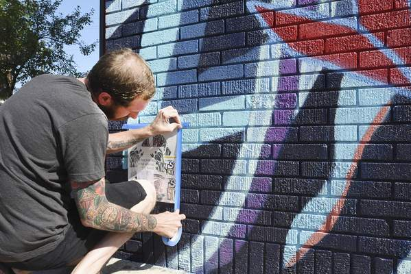 Jon Brown leaves free art on the wall of the Brass Rail as part of Fort Wayne Free Art Collective's art drop. (Photos by Cathie Rowand   The Journal Gazette)