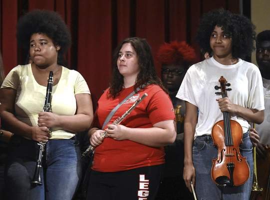 Students, from left, Angel Derrick, 15, Amber Driesse, 17, and Desaray Ekanem, 16, hold new instruments provided by a $500,000 donation. (Michelle Davies | The Journal Gazette)