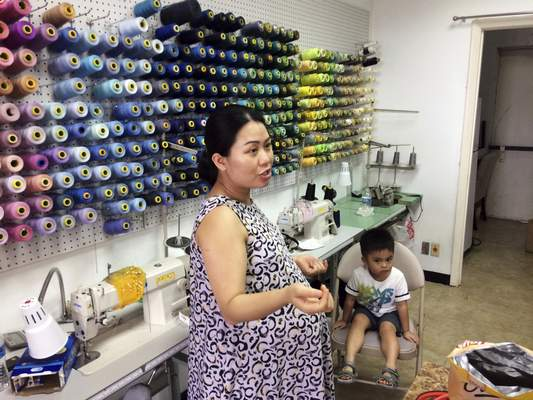 Associated Press Maria Tran, co-owner of Chic Tailors in Meyerland, Texas, prepares to open her business with her 3-year-old son, Ander. Tran wants to get the shop open quickly so her sister can take over while she gives birth to her second child, a daughter.