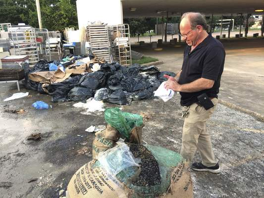 Bobby Jucker, owner of Three Brothers Bakery, cleans up the storm damage at his bakery in Houston. Harvey is the fifth storm to damage his business.
