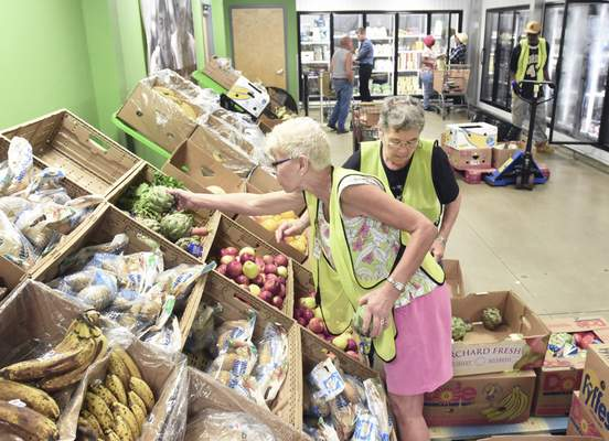 Cathie Rowand | The Journal Gazette Volunteers Charlene Nutter, front, and Ravenna Hapner stock produce at Community Harvest Food Bank of Northeast Indiana's  Community Cupboard last month.