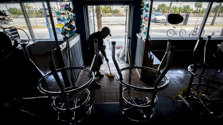 Fannie's By The Sea Manager Chris Jackson mops up his flooded restaurant Tuesday, Sept. 12, 2017, on Tybee Island, Ga., after Tropical Storm Irma flooded parts of the island. (AP Photo/Stephen B. Morton)