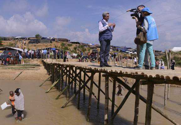 United Nations High Commissioner for Refugees Filippo Grandi gives an interview standing on a newly made bamboo bridge at Kutupalong, Cox's Bazar, Bangladesh, Saturday, Sept. 23, 2017. (AP Photo/Ziaul Haque Oisharjh)
