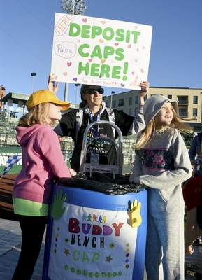 Rachel Von | The Journal Gazette Sammie Vance, 8, left, her mother Heidi Vance, center, and  Becca Eifrid, 10, collect bottle caps  for the Buddy Bench Cap Collection on Saturday.