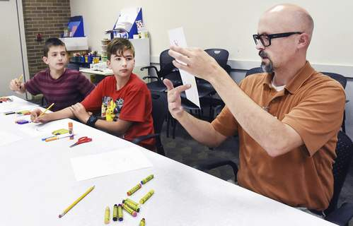 Cathie Rowand | The Journal Gazette  Nate Burnard, librarian at the Hessen Cassel branch library, teaches home-schoolers Isaac Walter, 11, and his brother Andrew, 12, about primary and secondary colors during a recent art class. (Cathie_Rowand)