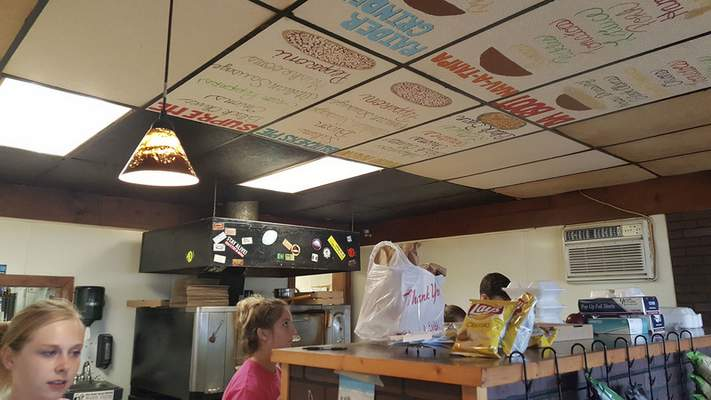 Employees work away below the cool instructioinal ceiling tiles in the kitchen of Puckerbrush Pizza in Payne, Ohio.