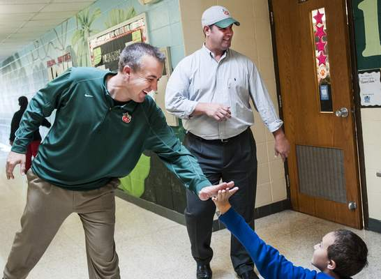 Nutter gives a high-five to fourth-grader  Winston Sellars while touring the school with Ankenbruck.