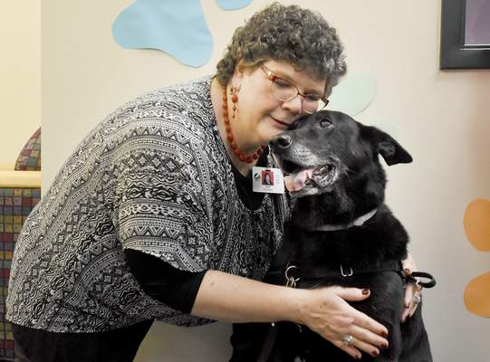 Rachel Von   The Journal Gazette Ruth Davis gives  her dog Piper a hug Thursday at the Pontiac branch of the Allen County Public Library. Davis, a human services assistant professor at Ivy Tech Community College of Indiana, and Piper, a Paws to Read dog for 10 years at Pontiac, were honored Thursday by branch staff.  The Paws to Read literacy program lets children read to dogs, and research has shown that  children who participate improve their reading skills.