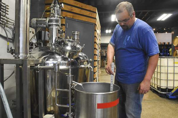 Patrick Tanesky, master distiller, checks how many gallons of bourbon have been distilled.