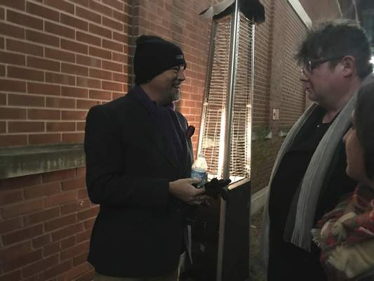 Jamie Duffy | The Journal Gazette  Jeff Kingsbury, a partnerat RTM Ventures, chats Friday with a Christmas on Broadway attendee at the Electric Works lighting.