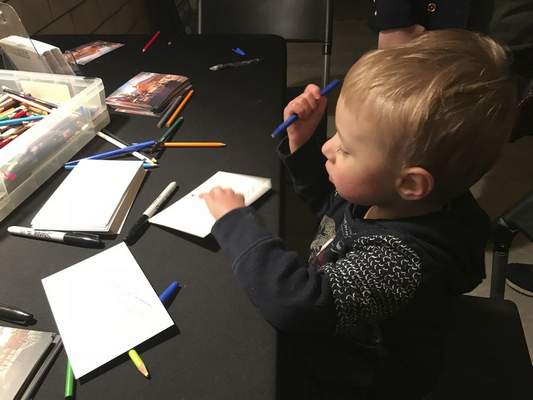 Jamie Duffy | The Journal Gazette  Robby Carpenter, 3, fills out a postcard at the Electric Works holiday festivities Friday. Robby came with his mom and dad, Brandon and Tabby Carpenter, and little sister Annabel, all of Huntertown.