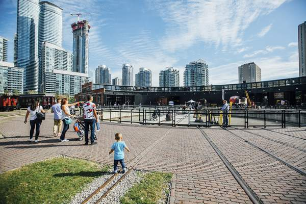 Families gather near the fully restored and operational locomotive turntable at Roundhouse Park, a 17-acre park in downtown Toronto.