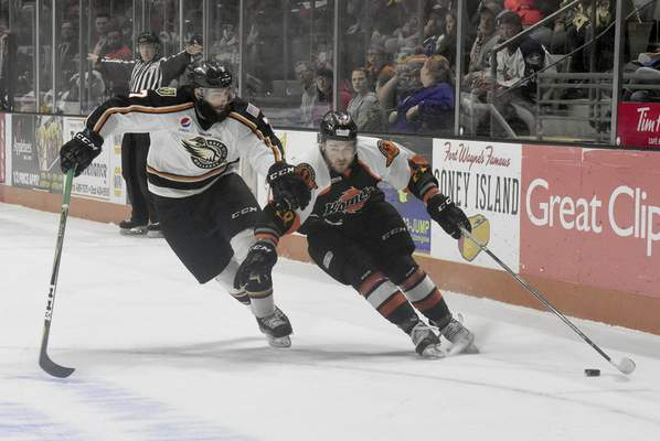 Rachel Von   The Journal Gazette  The Komets' Louick Marcotte, right, pushes past the Mallards' Jake Bolton during the first periodSaturday at theColiseum.