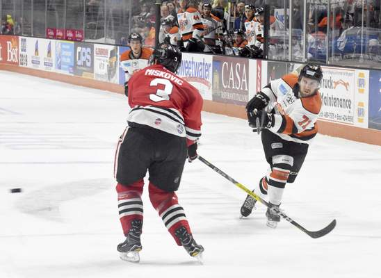 Rachel Von | The Journal Gazette  Komets' Ryan Lowney, right, shoots the puck past Fuel's Zach Miskovic during the first period of the game against Indy Fuel at Memorial Coliseum Saturday.