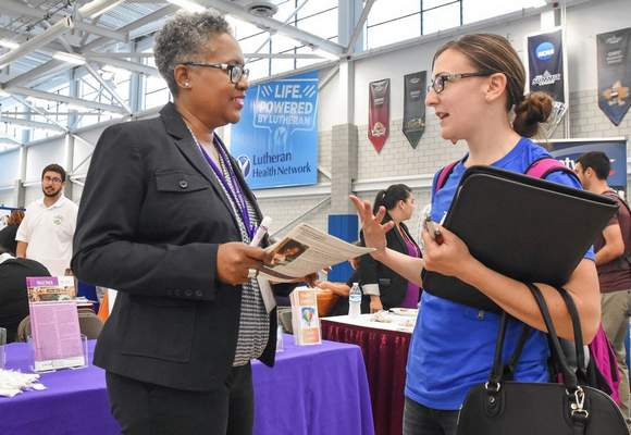 FILE:  Angelyss Auer, right, receives information about social work and counseling career opportunities from SCAN human resource manager Sonja Woods at the Mastodon Job and Internship Fair at IPFW.