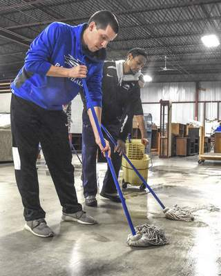 "University of Saint Francis basketball players Evan Henry, left, and James Mayberry mop  the warehouse at the Mustard Seed Furniture Bank on Monday as part of Saint Francis'  ""A Day On, Not A Day Off"" to celebrate MLK Day."