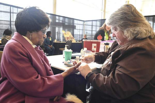 Martha Thomas, 90, left, gets a health screening from Jan Moore of Parkview during the celebration at Grand Wayne Center.