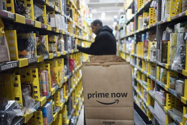 In this Wednesday, Dec. 20, 2017, file photo, a clerk reaches to a shelf to pick an item for a customer order at the Amazon Prime warehouse, in New York. (AP Photo/Mark Lennihan, File)