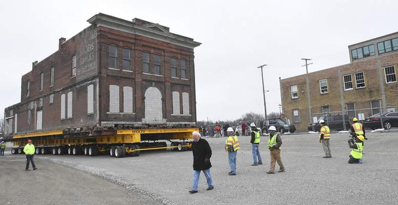 The former Cambray & Associates building is moved Monday from 312 S. Harrison St. to a temporary location at 124 W. Superior St. It will be moved to permanent spot this spring. (Photos by Cathie Rowand | The Journal Gazette)