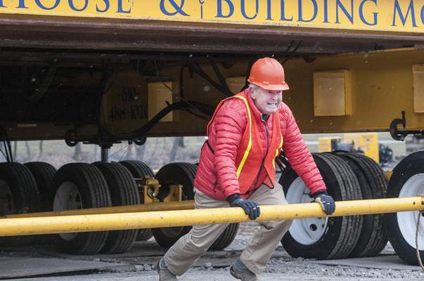 Bud Hall, co-owner of Hall's restaurants, playfully attempts to move the structure Monday. The Hall family bought the building in December but is not sure what they will do with it, though it could become a restaurant.