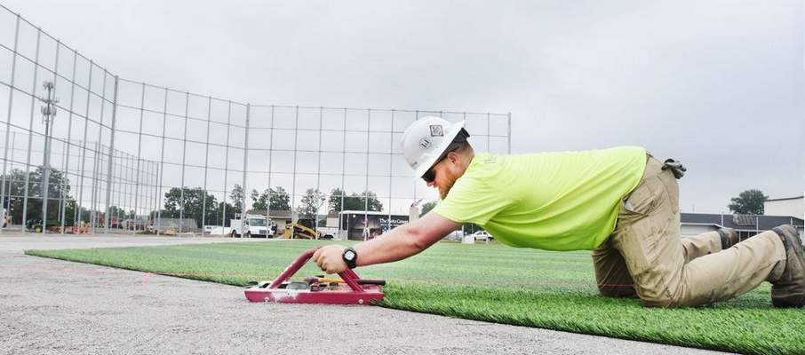 FILE: Bobby Elliott, of The Motz Group, installs artificial turf at the World Baseball Academy's fields at the ASH Centre.