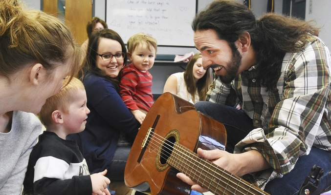 Photos by Cathie Rowand   The Journal Gazette Grady Abbott, 2, gets a chance to learn about Cote Godoy's guitar during Musical Conexion, a bilingual music and movement program, Tuesday at the Aboite branch of the Allen County Public Library.