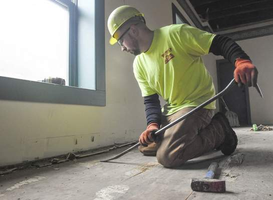 Michelle Davies   The Journal Gazette Mark Jones works on removing the sub flooring of a building at 131 West Columbia Street Thursday afternoon.