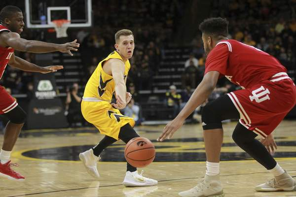 Iowa's Jordan Bohannon passes to Tyler Cook, not pictured, during an NCAA college basketball game against Indiana, Saturday, Feb. 17, 2018 in Iowa City, Iowa. (David Scrivner/Iowa City Press-Citizen via AP)