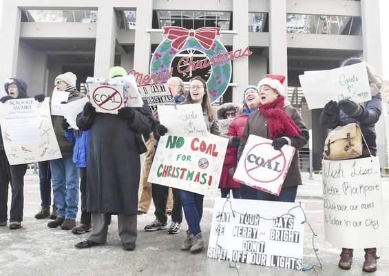 In a Dec. 14 protest, local residents sing Christmas carols with altered lyrics at Indiana Michigan Power's downtown headquarters to demonstrate against higher utility bills and coal pollution.