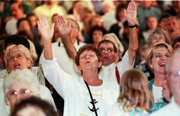 File Fort Wayne residents, from left, Marty Rutan, Lil Howenstine and Jan Clymer raise their hands at a 1999 Billy Graham Crusade at the RCA Dome in Indianapolis.