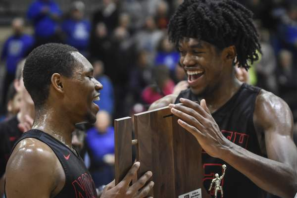 Mike Moore | The Journal Gazette North Side guard Brandan Johnson, left and Keion Brooks are presented with the IHSAA sectional championship trophy at East Noble high school on Saturday.