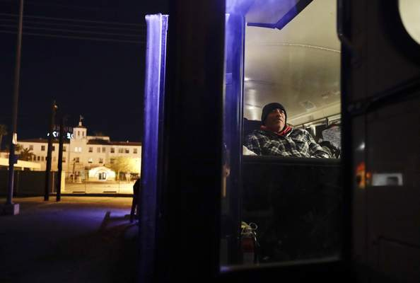 In this March 6, 2018 photo, farmworker Jose Angel Valenzuela rests as he waits before dawn in a bus that will take him and his crew from the border in Calexico, Calif, to a cabbage field ready for harvest outside of town.  (AP Photo/Gregory Bull)