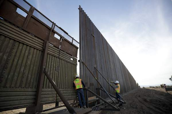In this March 5, 2018, photo, a worker looks between the first section of a newly-constructed structure along the border separating Mexicali, Mexico and Calexico, Calif. (AP Photo/Gregory Bull)
