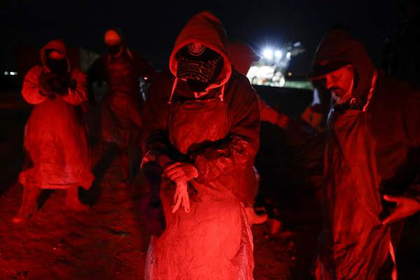 In this March 6, 2018 photo, farmworker Eduardo Garcia, of Mexicali, Mexico, center, puts on an apron and gloves in the glow from the taillights of a bus, as he and his crew arrive at a cabbage field ready for harvest, before dawn outside of Calexico, Calif.  (AP Photo/Gregory Bull)