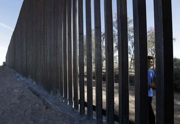 In this March 5, 2018, photo, a boy looks through the first section of a newly-constructed structure along the border separating Mexicali, Mexico, right, and Calexico, Calif.  (AP Photo/Gregory Bull)