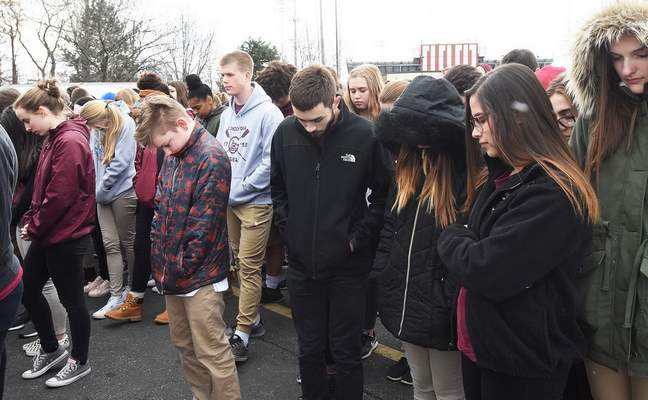 Concordia High School students pray as they participate in the National School Walkout Wednesday in remembrance of 17 individuals who lost their lives at Marjory Stoneman Douglas High School in Parkland, Florida, one month ago.