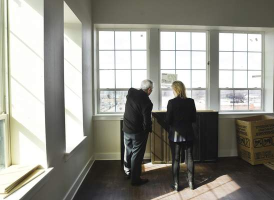 Mayor Tom Henry and Real America CEO/President Ronda Weybright look out at the view from a corner apartment that faces Superior and Harrison streets during a tour for officials Wednesday. (Photos by Cathie Rowand | The Journal Gazette)