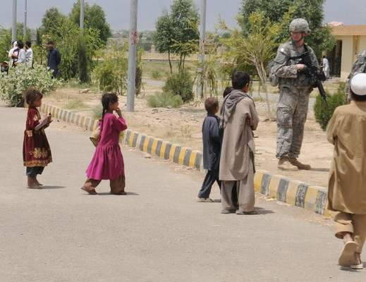 Courtesy Jeremy Gulley Jeremy Gulley stands guard as children walk to school in Afghanistan. Gulley, commanding officer of an Indiana National Guard battalion, was deployed to Afghanistan in 2010-11.