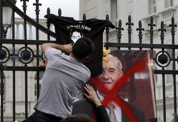 A man places a poster with a headshot of Macedonia's Public Prosecutor Ljubomir Joveski and a T-shirt with the image of Almir Aliu with the words ''I am Almir'' at the entrance of the government building during a rally in Skopje, Wednesday, March 21, 2018. Macedonia's justice minister has resigned following public outcry over the case of a 4-year-old boy killed nearly two years ago, after a prosecutor reduced the charges against the driver of the car that hit the child. More than 1,000 people gathered to protest the reduced charges. (AP Photo/Boris Grdanoski)