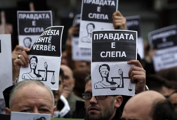 People hold banners reading in Macedonian and Albanian The Justice is blind during a rally outside the government building in Skopje, Wednesday, March 21, 2018. Macedonia's justice minister has resigned following public outcry over the case of a 4-year-old boy killed nearly two years ago, after a prosecutor reduced the charges against the driver of the car that hit the child. More than 1,000 people gathered to protest the reduced charges. (AP Photo/Boris Grdanoski)