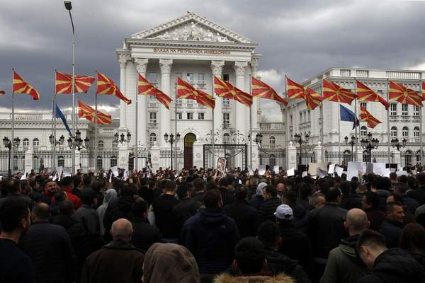 People take part in a rally outside the government building in Skopje, Wednesday, March 21, 2018. Macedonia's justice minister has resigned following public outcry over the case of a 4-year-old boy killed nearly two years ago, after a prosecutor reduced the charges against the driver of the car that hit the child. More than 1,000 people gathered to protest the reduced charges. (AP Photo/Boris Grdanoski)