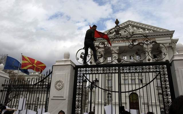 A man places an Albanian flag at the entrance of the government building during a rally in Skopje, Wednesday, March 21, 2018. Macedonia's justice minister has resigned following public outcry over the case of a 4-year-old boy killed nearly two years ago, after a prosecutor reduced the charges against the driver of the car that hit the child. More than 1,000 people gathered to protest the reduced charges. (AP Photo/Boris Grdanoski)