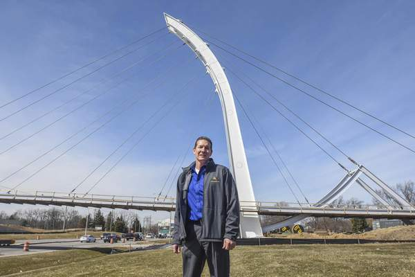 Michelle Davies   The Journal Gazette Kurt Heidenreich, president of Engineering Resources Inc., stands in front of the Parker Cole Crossing, the pedestrian bridge  he designed that will link IPFW with Ivy Tech. The bridge is scheduled to be completed in July.