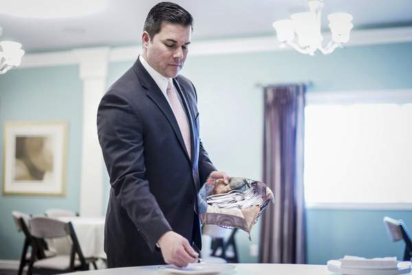 Mike Moore   The Journal Gazette D.O. McComb & Sons location manager Lucas Glessner sets  tables for catering services at McComb's East Dupont Road funeral home.