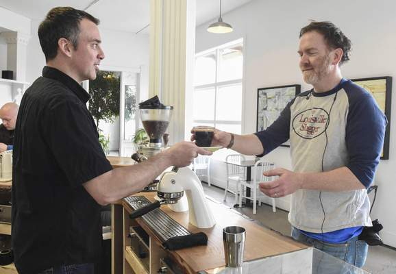 Michelle Davies | The Journal Gazette Corey Waldron, left, hands Conjure Coffee customer Weston Cutter his coffee Friday. Waldron has strived to have a customer-friendly coffee shop, which he's helped accomplish with Modbar.