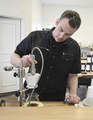 Michelle Davies | The Journal Gazette Corey Waldron, owner of Conjure Coffee and Modbar co-founder, makes a pour over coffee with faucet-like hardware he designed.